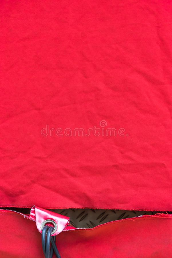 Um encerado vermelho puro amarrotado com um furo e um furo fotos de stock