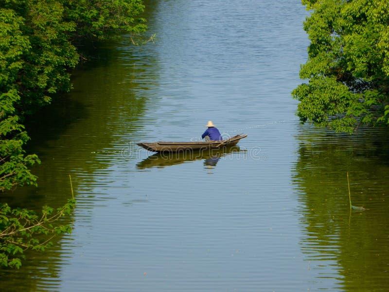 Um enfileiramento do pescador em um rio fotografia de stock royalty free