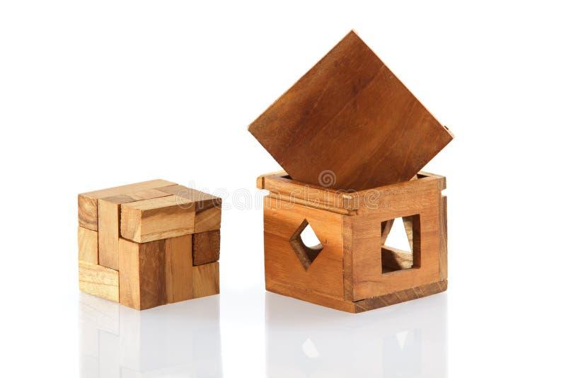 Um enigma de madeira é um cubo Isolado no fundo branco Close-up fotografia de stock royalty free