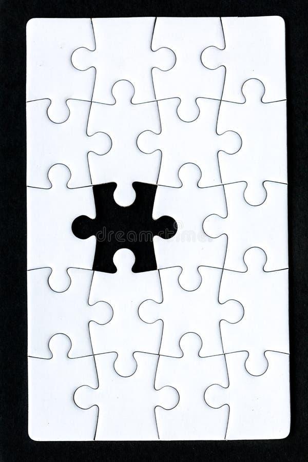 Um enigma essa uma parte faltante contra um fundo preto imagem de stock