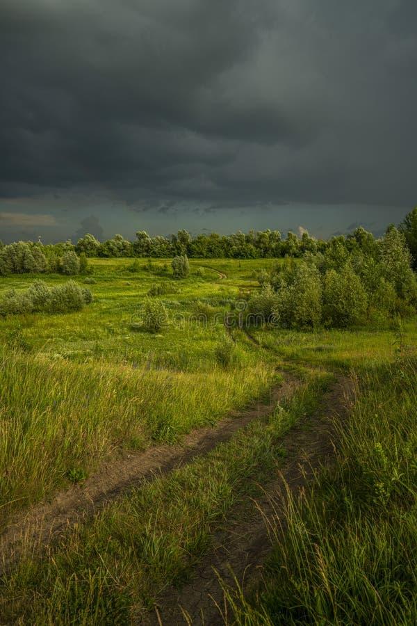 Um enrolamento, uma estrada rural da sujeira correndo através de um prado iluminado pela luz solar, e acima dela um céu tormentos fotografia de stock