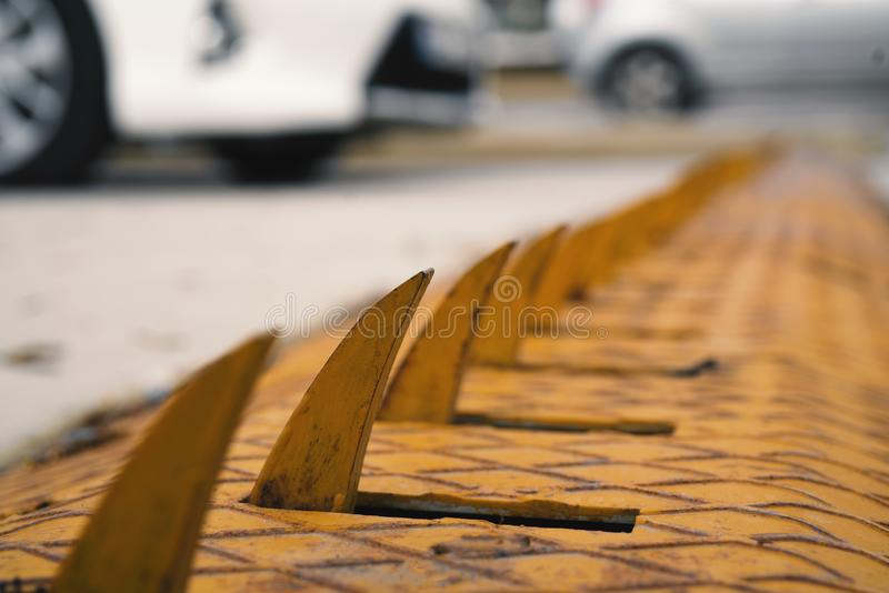 Um equipamento muito perigoso do controle do sentido do carro em amarelo e em vermelho com os pinos de aço do metal afiado em cru fotografia de stock