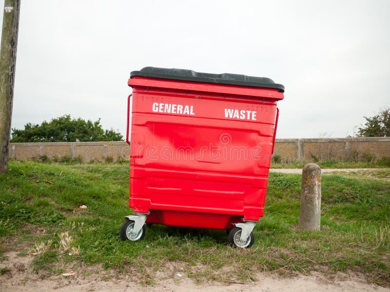 Um escaninho waste geral vermelho escolhe uma parte externa na grama imagem de stock