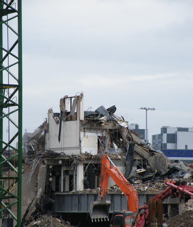 um escavador alaranjado com um funcionamento do backhoe em um grande local de demolição urbano com um guindaste de torre do metal fotos de stock