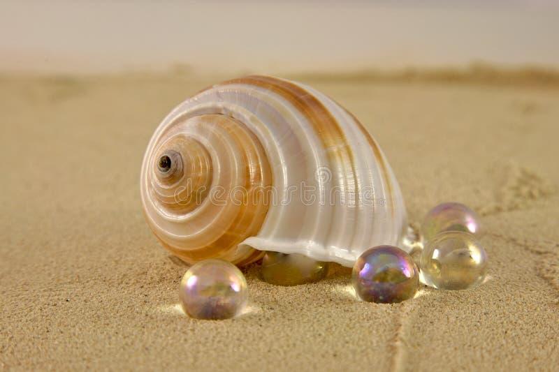 Um escudo e mármores na areia da praia foto de stock