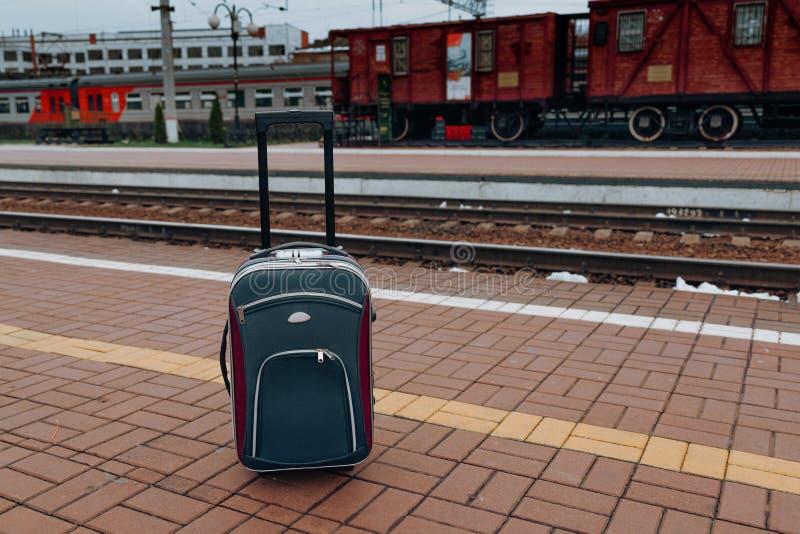 Um escuro - a mala de viagem azul nas rodas está em uma plataforma de partida do trem, um fundo das reflexões, fotografia de stock royalty free