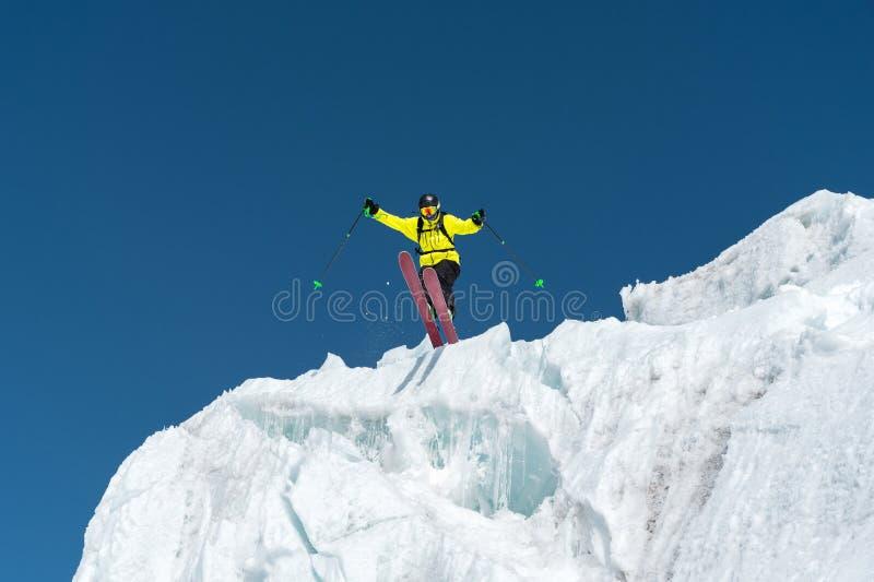 Um esquiador de salto que salta de uma geleira contra um azul muito ao alto nas montanhas Esqui profissional fotografia de stock royalty free