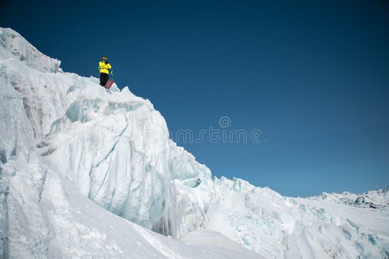 Um esquiador freerider no equipamento completo está em uma geleira no Cáucaso norte Esquiador que prepara-se antes de saltar do imagem de stock