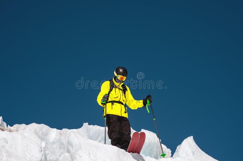 Um esquiador freerider no equipamento completo está em uma geleira no Cáucaso norte Esquiador que prepara-se antes de saltar do fotos de stock