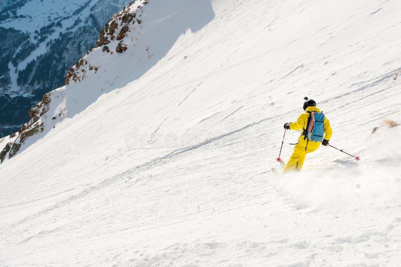 Um esquiador masculino freerider com uma barba desce o backcountry na alta velocidade da inclinação fotografia de stock