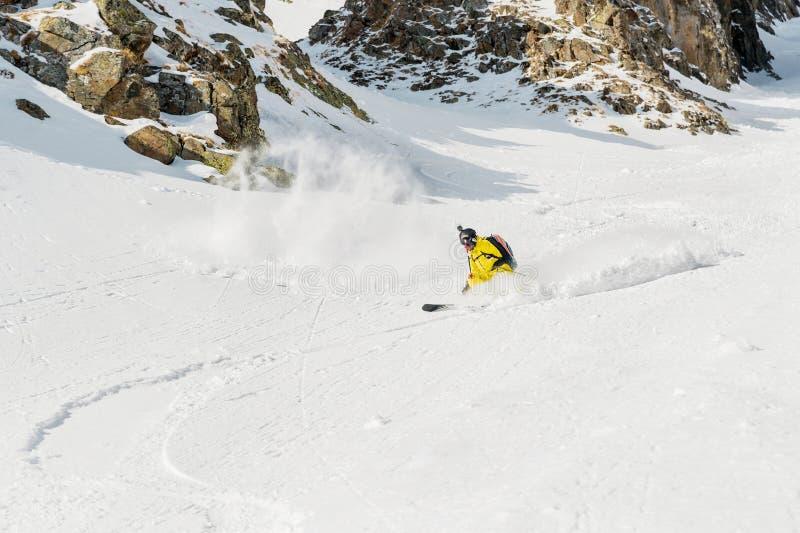 Um esquiador masculino freerider com uma barba desce o backcountry na alta velocidade da inclinação imagens de stock royalty free
