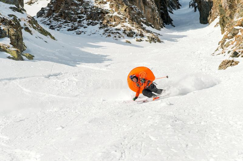 Um esquiador masculino freerider com uma barba desce o backcountry na alta velocidade da inclinação imagem de stock