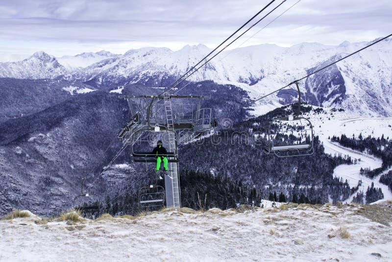 Um esquiador solitário escala as montanhas em um teleférico para a descida imagem de stock royalty free