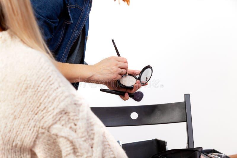 Um estilista no trabalho em um estúdio da composição escolhe um produto cosmético de uma paleta com um close-up da escova pega o  imagens de stock royalty free