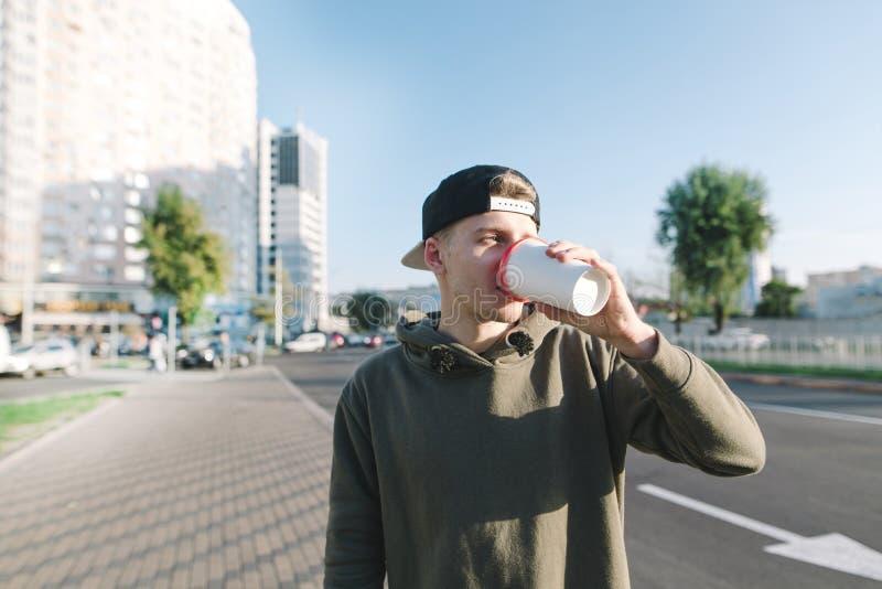 Um estudante bebe uma bebida quente para uma caminhada em torno da cidade O homem novo está no fundo da rua e bebe o café Estilo  imagens de stock