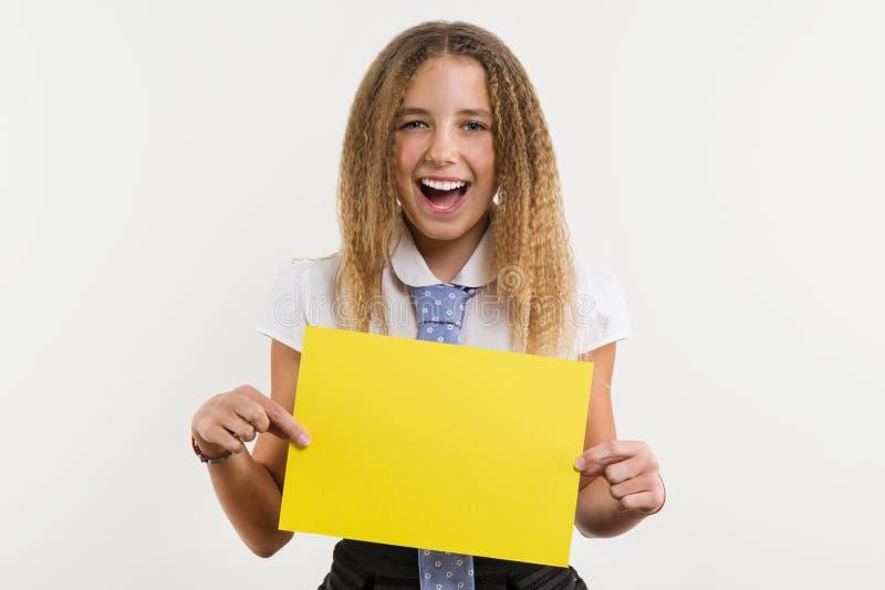 Um estudante de sorriso da High School, louro com cabelo encaracolado, guarda um papel vazio da cor amarela, em que pode estar se imagem de stock