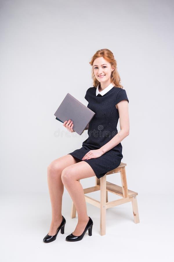 Um estudante f?mea caucasiano bonito novo senta-se em uma cadeira no est?dio em um fundo branco Est? vestindo um vestido imagens de stock