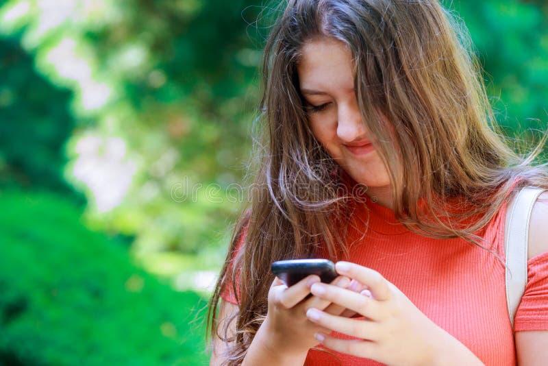 Um estudante feliz que anda e que usa o telefone esperto na linha na rua no por do sol com uma leitura adolescente bonita clara m imagem de stock