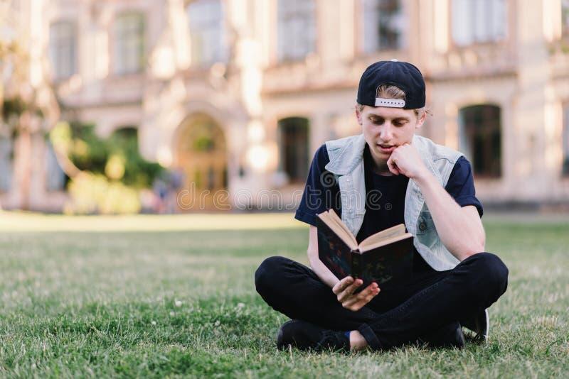 Um estudante lê com cuidado um livro que senta-se em uma grama em um parque perto de uma faculdade Adolescente que lê um livro fo imagens de stock royalty free