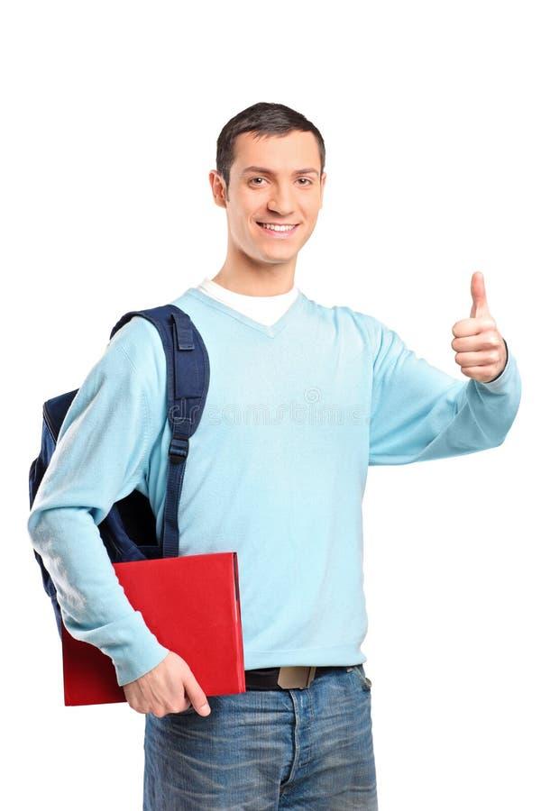 Um estudante masculino que prende um livro e que dá o polegar acima foto de stock royalty free