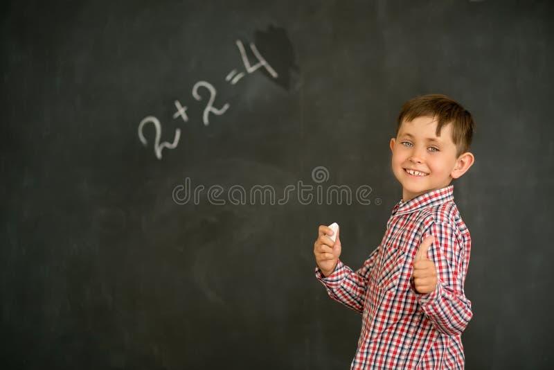 Um estudante pequeno e alegre resolveu o problema na placa e mostra seus polegares acima fotos de stock royalty free