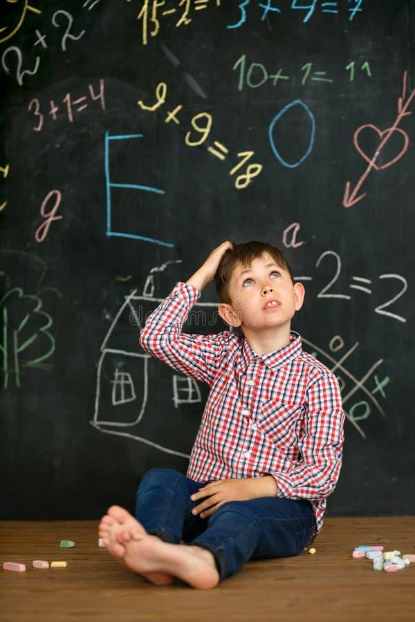 Um estudante pequeno resolve uma tarefa dificil imagem de stock