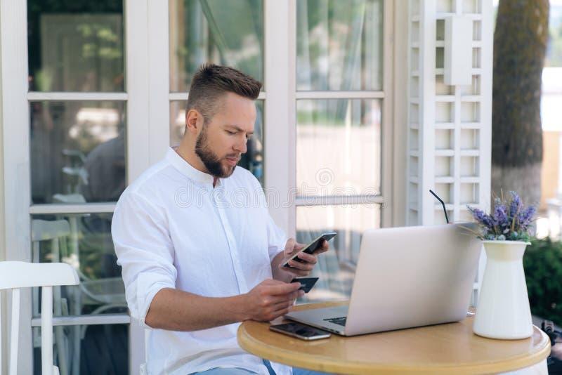 Um europeu masculino considerável está sentando-se fora em um café, trabalhando em um portátil, fazendo compras através do Intern imagem de stock royalty free