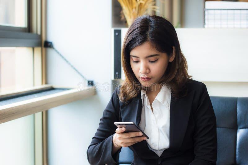 Um executivo de mulher asiático bonito do negócio que relaxa na cafetaria que realiza e que usa uma aplicação em seu telefone esp imagem de stock royalty free