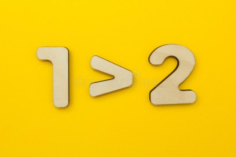 Um exemplo matemático errôneo para crianças em um fundo amarelo Um é mais de dois fotos de stock royalty free