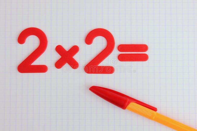 Um exemplo matemático simples em um caderno limpo da escola De volta ? escola fotos de stock