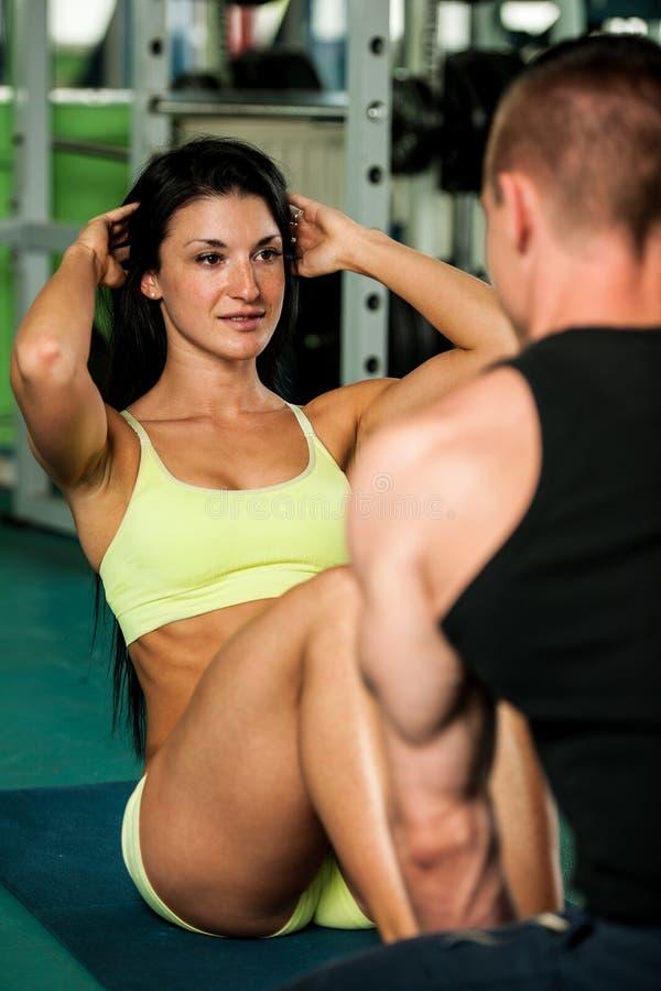 Um exercício dos pares da aptidão - mann e a mulher aptos treinam no gym imagem de stock
