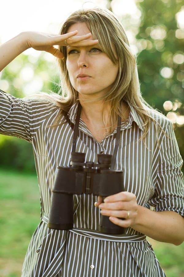 Um explorador da mulher está usando os binóculos pretos - exteriores imagem de stock