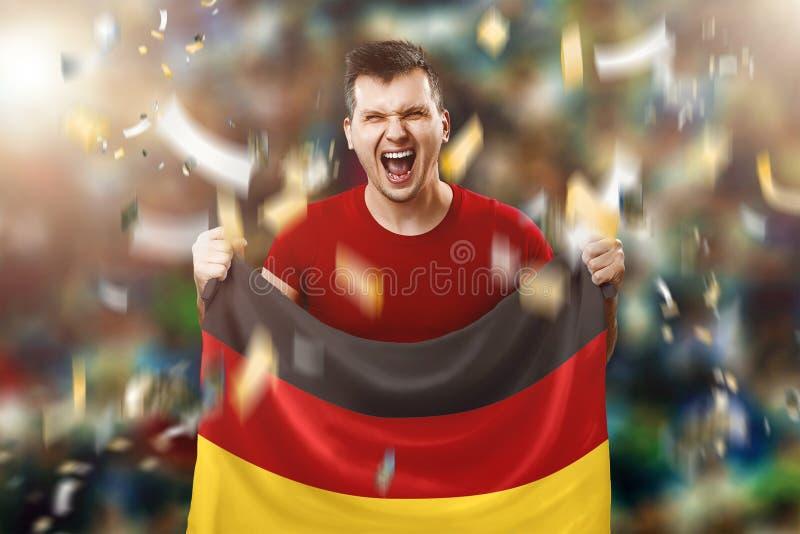 Um fã alemão, um fã de um homem segurando a bandeira nacional da Alemanha em suas mãos Fã de futebol no estádio Mídia mista imagem de stock royalty free
