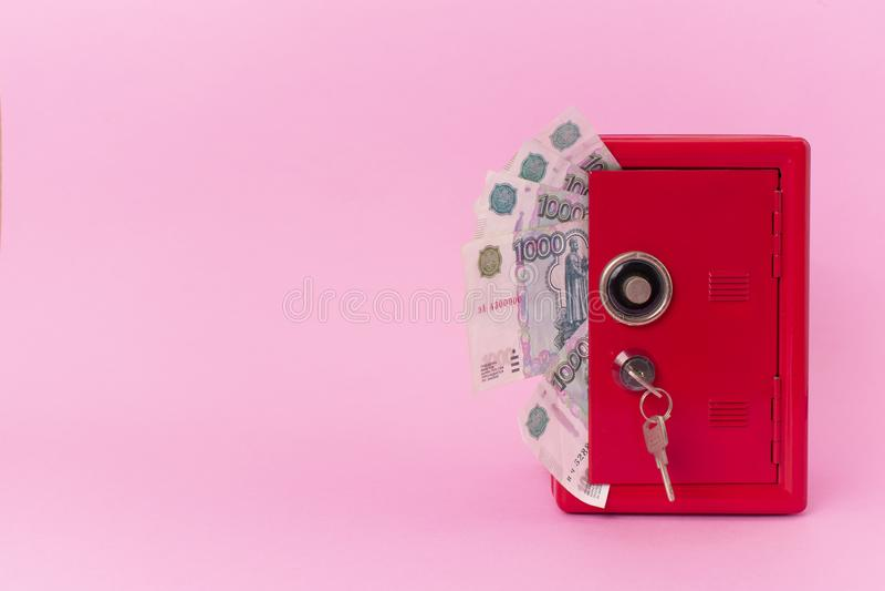 Um fã do dinheiro do russo dentro do cofre forte vermelho no fundo cor-de-rosa banco com chave foto de stock