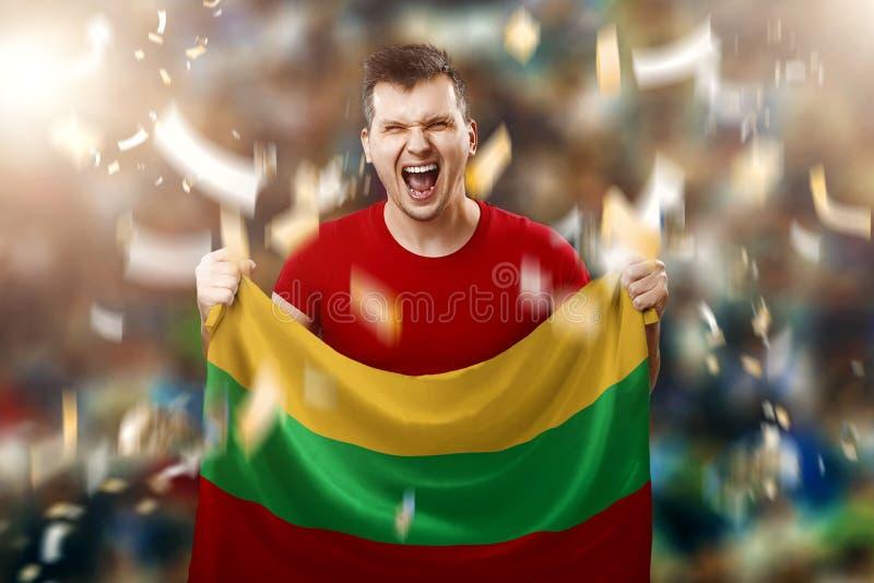 Um fã lituano, um fã de um homem que segura a bandeira nacional da Lituânia nas suas mãos Fã de futebol no estádio Mídia mista foto de stock