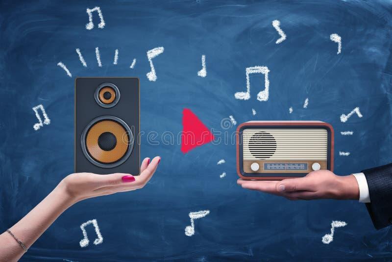 Um fêmea e mãos masculinas que guardam um orador audio moderno e um grupo de rádio retro fotos de stock