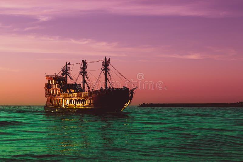 Um fabuloso navio vintage dourado navegando num mar verde surreal contra um púrpura - céu vermelho, conceito de contos de fadas e imagem de stock royalty free