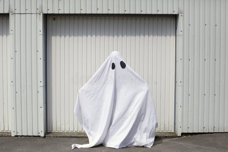 Um fantasma na frente de uma porta da garagem fotografia de stock
