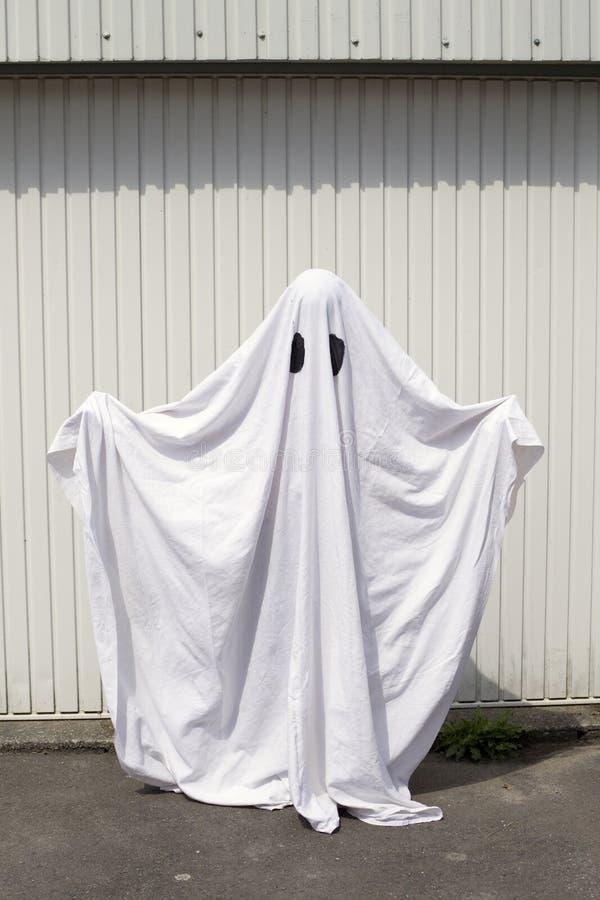 Um fantasma na frente de uma porta da garagem imagens de stock royalty free