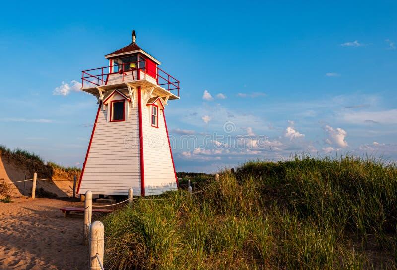 Um farol na praia com luz de hora dourada fotos de stock royalty free