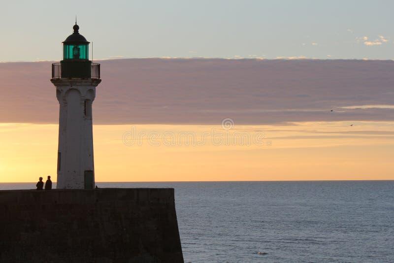 Um farol no mar com cores bonitas no céu foto de stock