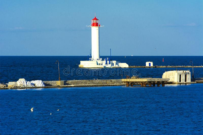 Um farol no mar na entrada ao porto contra imagem de stock royalty free