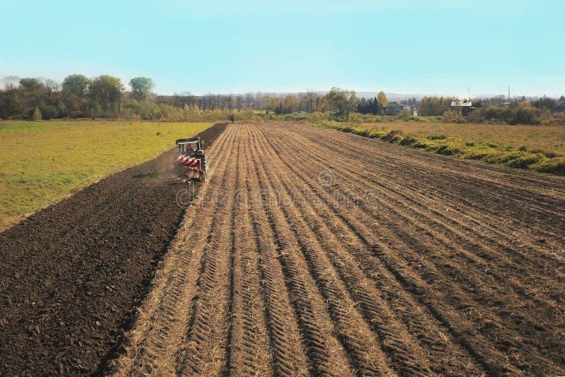Um fazendeiro em um trator vermelho com uma máquina de semear semeia a grão na terra arada em um campo privado na área da vila Me fotografia de stock