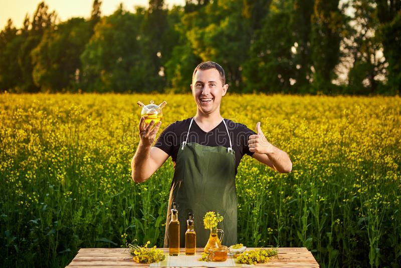 Um fazendeiro ou um agrônomo do homem novo examinam a qualidade do óleo de colza em um campo da violação Conceito do neg?cio agr? fotografia de stock