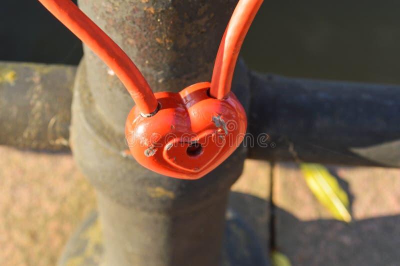 Um fechamento vermelho do celeiro na forma de um coração pendura nos trilhos de uma ponte Tradição do casamento para pendurar fec foto de stock royalty free