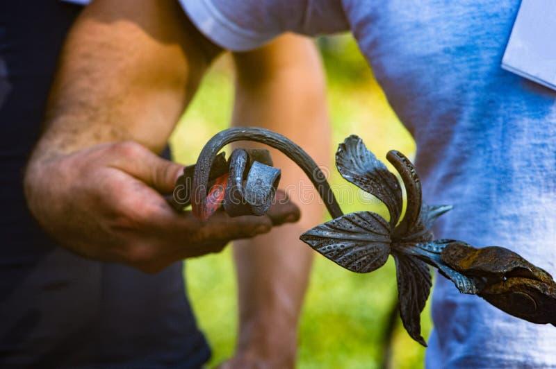 um ferreiro faz do metal que quente o ferro original aumentou imagens de stock