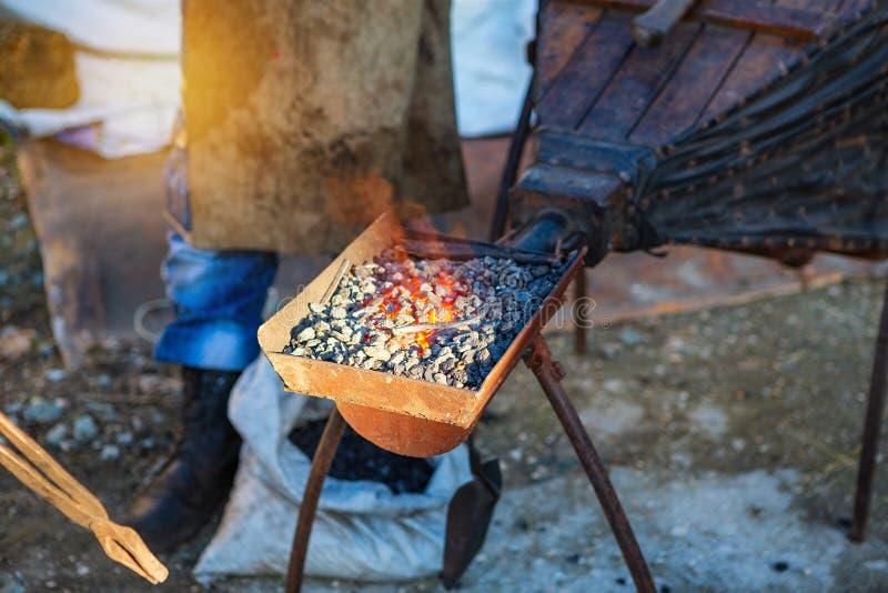 Um ferreiro forja o ferro na forja, nos tenazes de brasa e no martelo imagem de stock