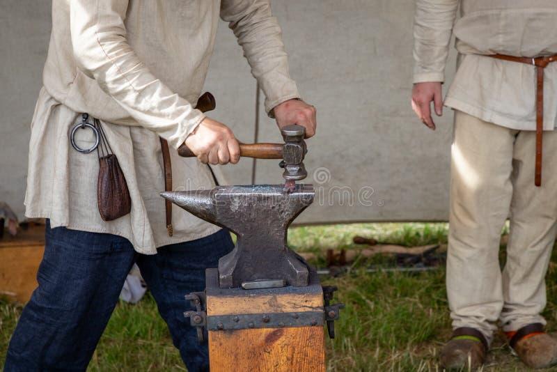 Um ferreiro medieval forja o ferro em um batente imagens de stock
