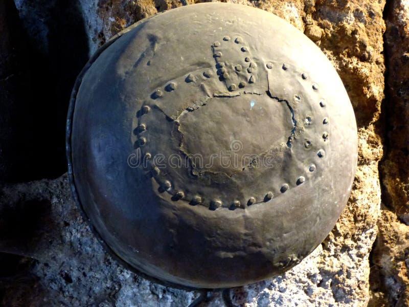 Um ferro rebitou o potenciômetro usado pelo Etruscans que pendura em uma coluna de pedra fotos de stock royalty free
