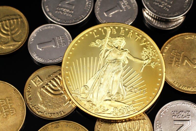 Um fim acima da imagem de uma variedade de moedas israelitas com uma uma moeda de ouro americana da onça em um fundo preto imagens de stock royalty free